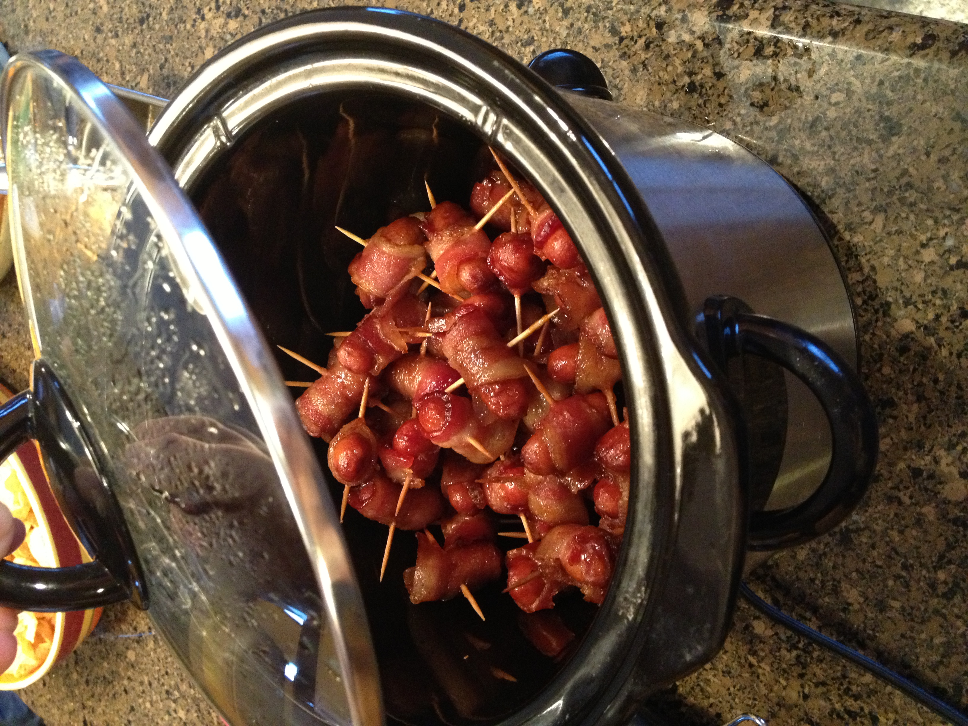 You don't have to use toothpicks, but if you do, don't use the colored ones. The dye from the colored toothpicks cooks off on the bacon. Place the bacon wrapped smokies in the crock pot, seam side down.